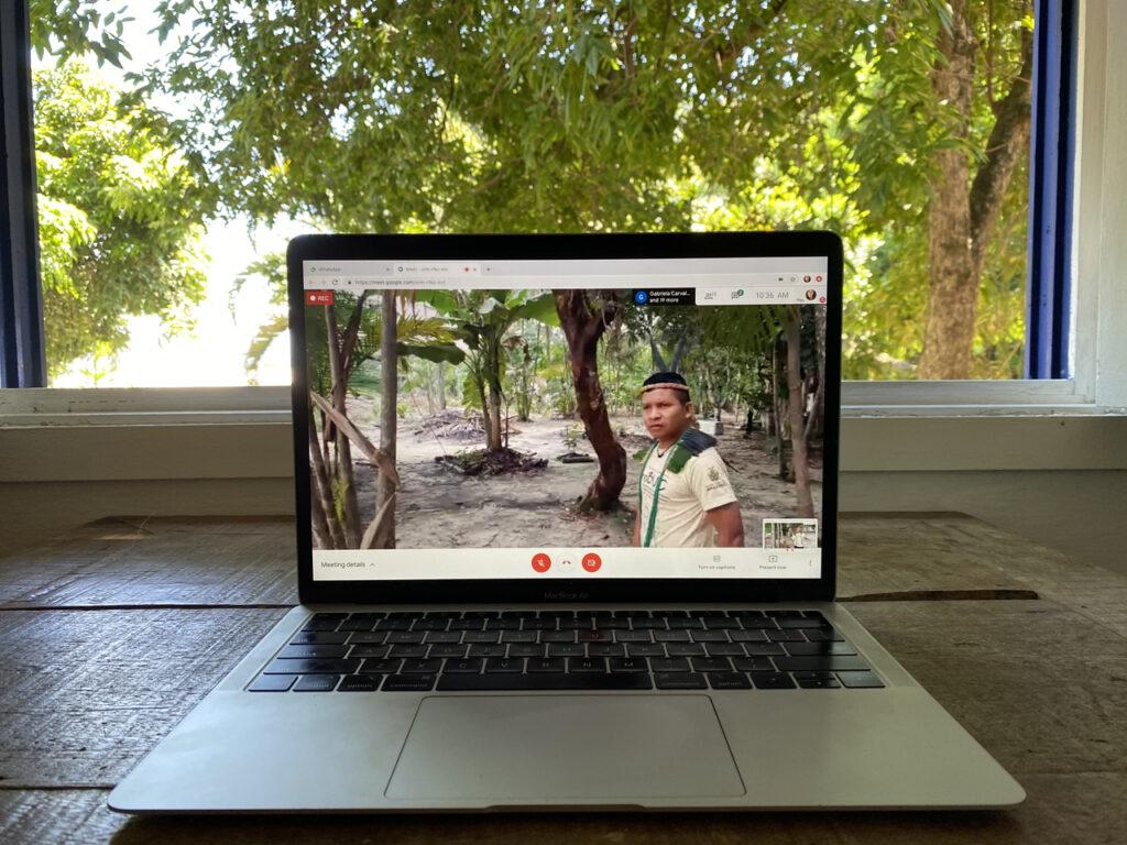 Imagem mostra um computador ao centro com a imagem de um comunitário indígena entre algumas árvores da aldeia. Ao fundo do computador há uma janela aberta exibindo as folhas das árvores.