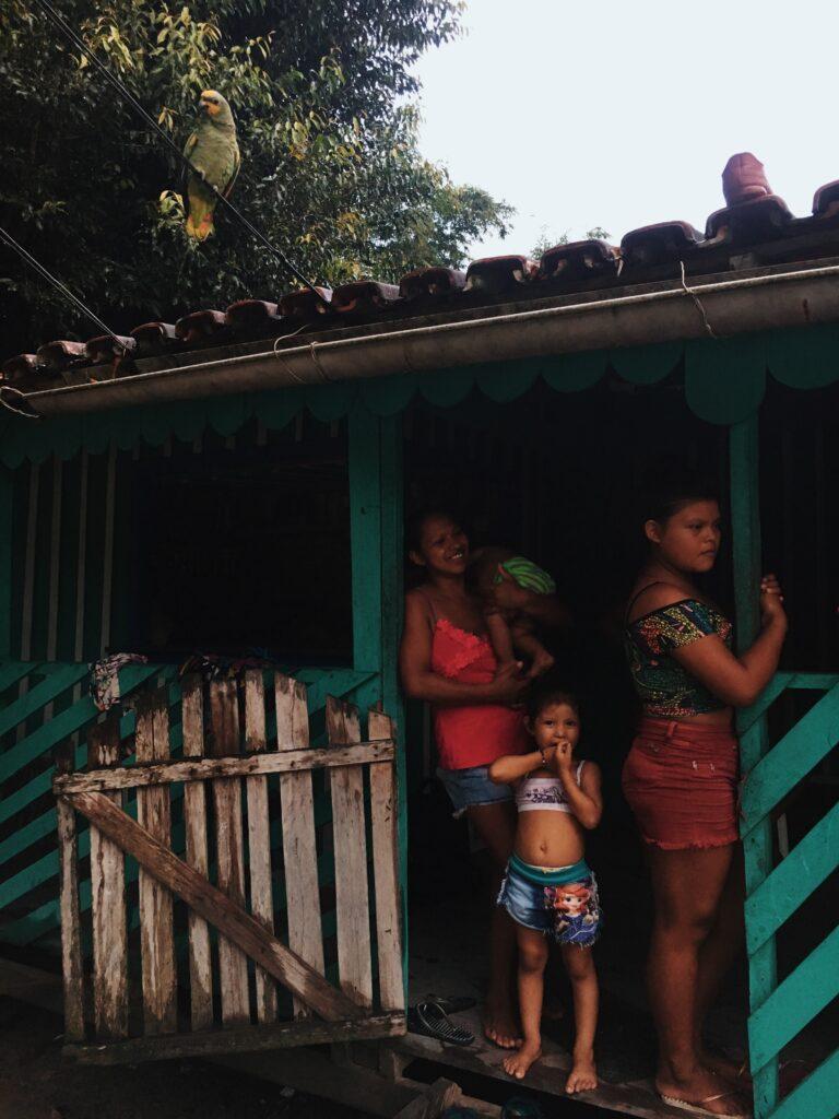 Imagem de três mulheres da comunidade Baré na varanda de uma casa. Na esquerda, uma mulher segurando um bebê, no centro uma criança e à direita, uma adolescente segurando o batente de madeira azul da entrada da casa.