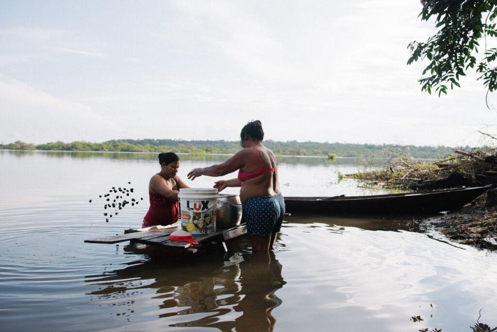Imagem de duas moradoras da comunidade Baré na beira do rio, trabalhando em uma superfície de madeira com alguns utensílios.