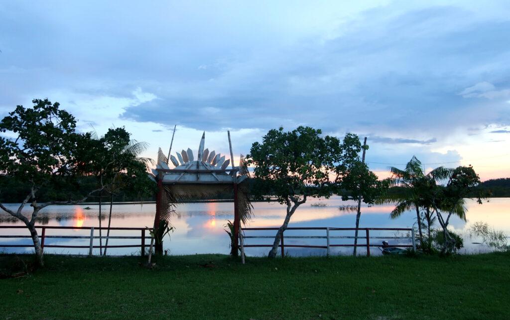 Imagem da entrada da comunidade, sob a perspectiva de quem olha de dentro dela, com algumas árvores e o rio. Ao fundo, o pôr do sol reflete nas águas do rio.