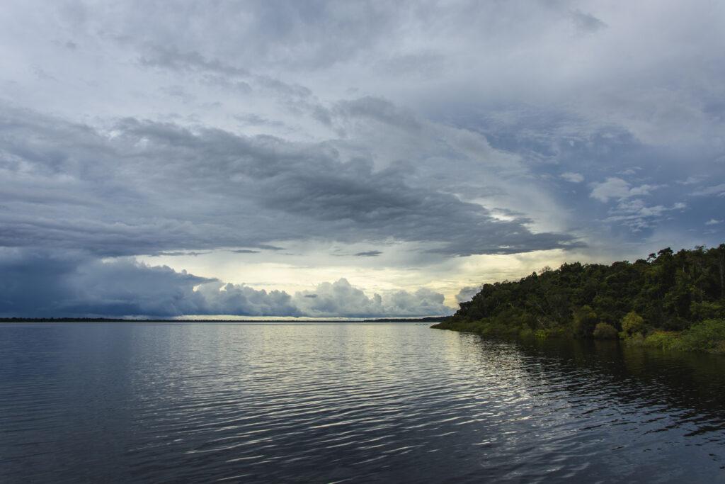 Imagem de um rio com água escura sob um céu com muitas nuvens. No canto direito, um pedaço da floresta.